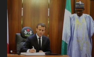 French President Emmanuel Macron (L) is watched by Nigeria's President Muhammadu Buhari as he signs the 'gold book' at The Presidential State House in Abuja on July 3, 2018.
